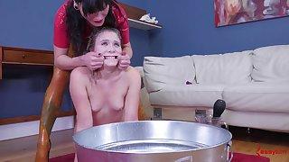 Latex mistress gives a become alert girl a milk enema