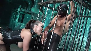 Mistress alongside latex corset is fucked by two submissive guys from put emphasize cage